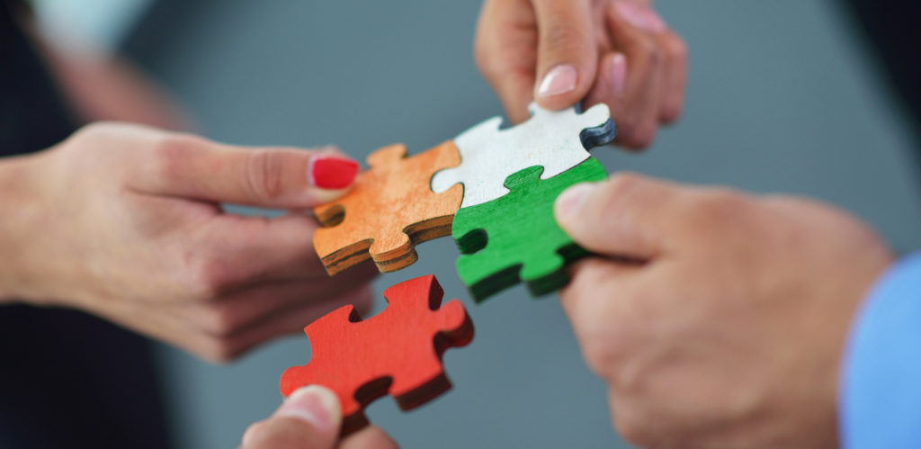 Collaboration. Group of business people assembling jigsaw puzzle.